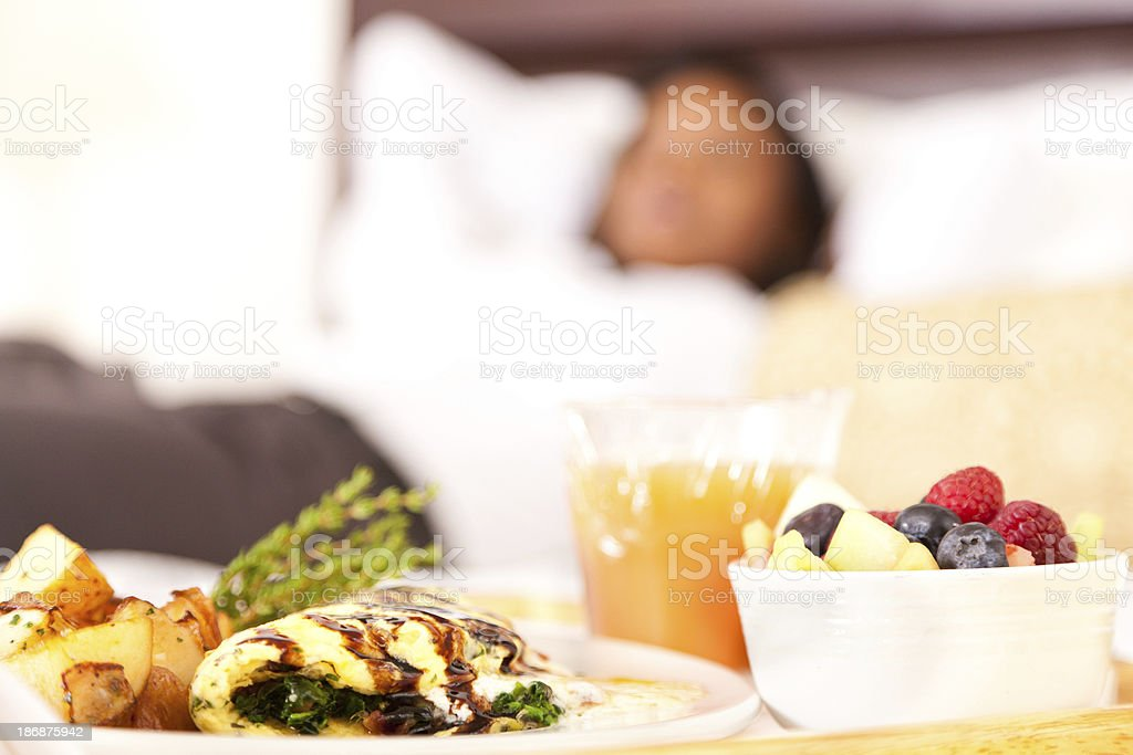 Breakfast laid out for woman relaxing in upscale hotel room stock photo
