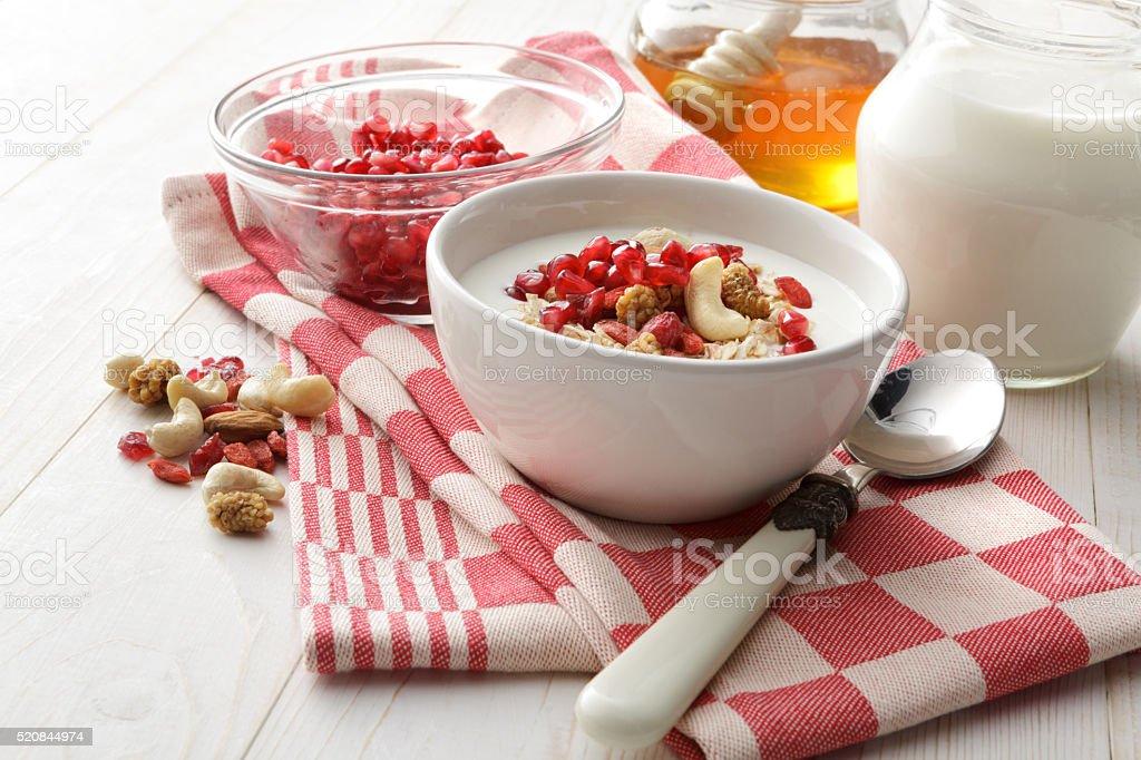 Breakfast: Muesli, Pomegranate, Yogurt and Honey Still Life stock photo