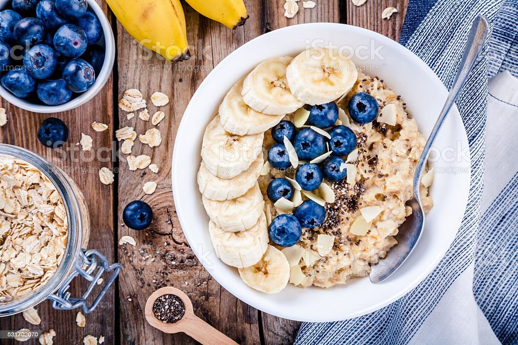 Breakfast: oatmeal with bananas, blueberries, chia seeds and almonds stock photo