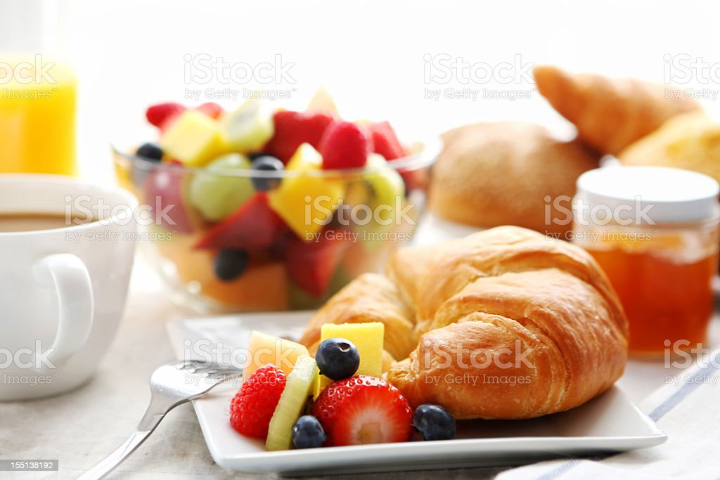 Breakfast of croissant, fruit salad, and coffee stock photo
