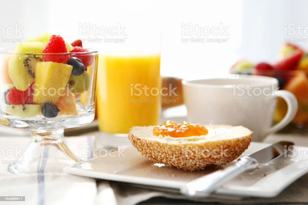 A breakfast of fruit bagel with jam orange juice and coffee stock photo