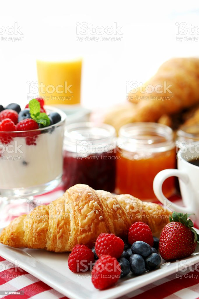 Breakfast of fruit, juice, yogurt, croissant and coffee stock photo