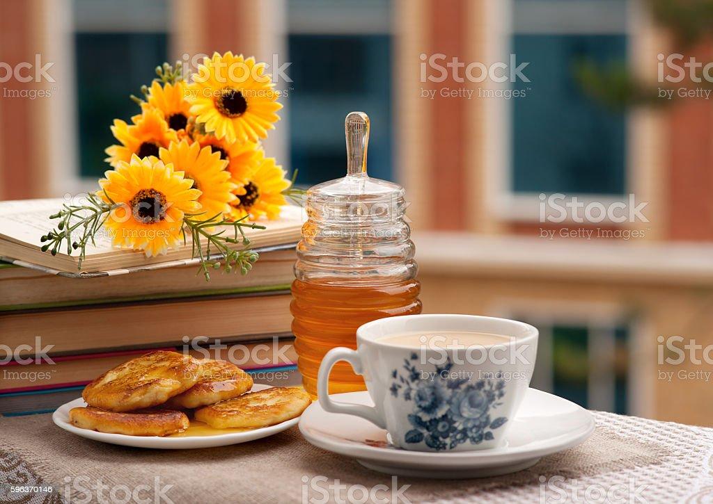 Breakfast of pancakes, honey and tea on the balcony. stock photo