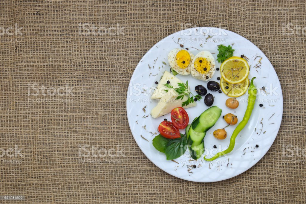 Breakfast Plate with Cherry Tomato, Egg, Cheese, Green Pepper, Olive, Bassil, Parsley, Black Peppercorn stock photo