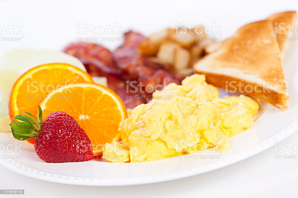 A breakfast plate with scrambled eggs, toast, and bacon stock photo