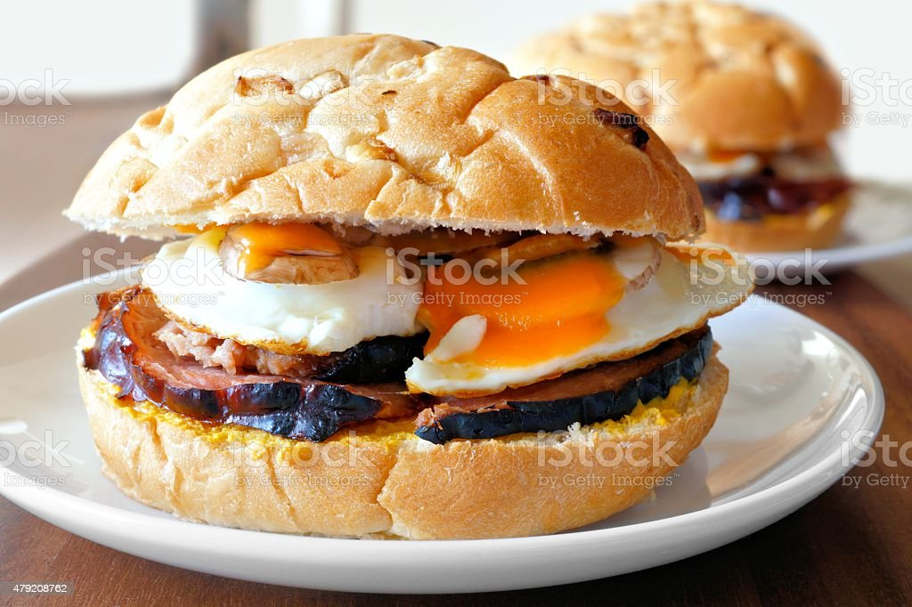 Breakfast sandwich with eggs, ham, mushrooms and cheese stock photo