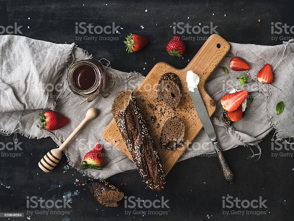 Breakfast set. Black baguette toasts with fresh strawberries, honey and stock photo