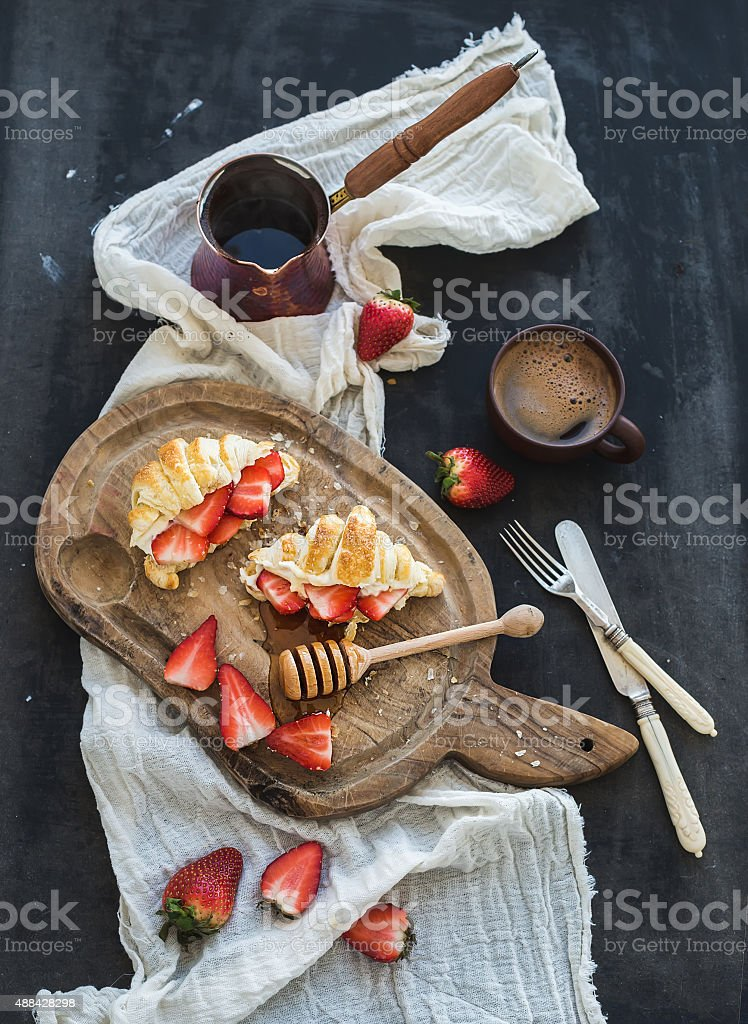 Breakfast set. Freshly baked croissants with strawberries, mascarpone, honey and stock photo
