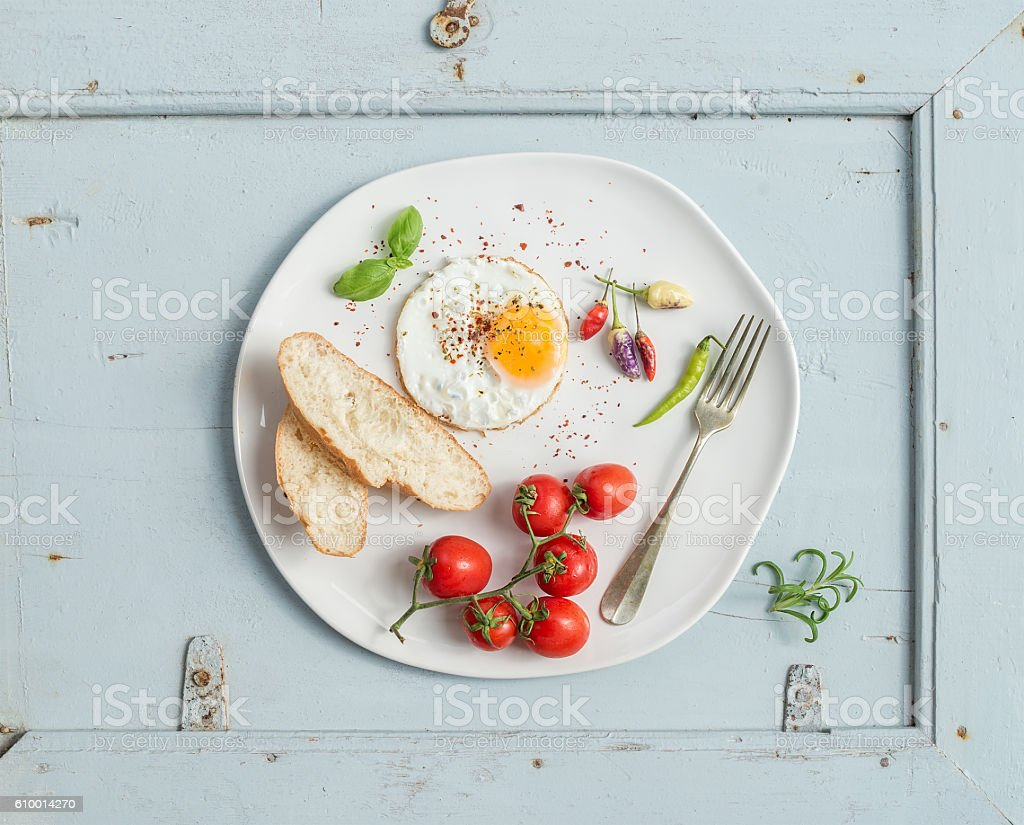 Breakfast set. Fried egg, bread slices, cherry tomatoes, hot peppers stock photo