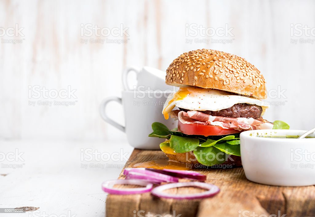 Breakfast set. Homemade beef burger with fried egg, vegetables, onion stock photo