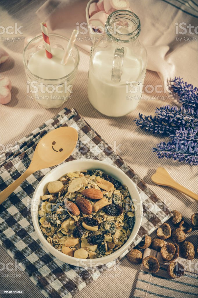 Breakfast set. mix oat granola in white bowl with pink heart sweet marshmallow on table set background, serve with white milk in glass and Bottle, top view, Healthy food concept, vintage tone color stock photo