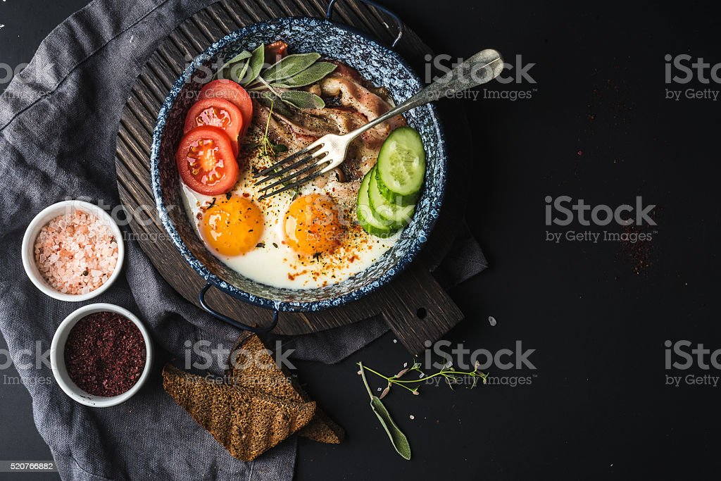 Breakfast set. Pan of fried eggs with bacon, fresh tomato stock photo