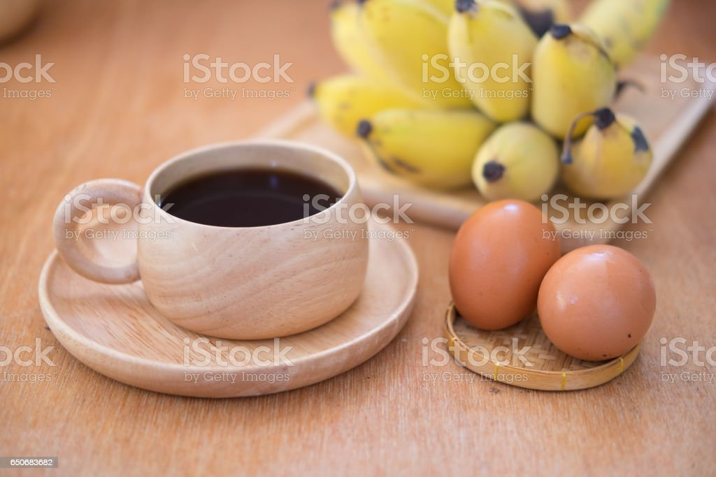 Breakfast set. Soft-boiled egg and banana with hot coffee on wood table stock photo