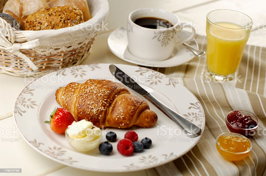 Breakfast spread of croissant coffee bread rolls and juice royalty-free stock photo