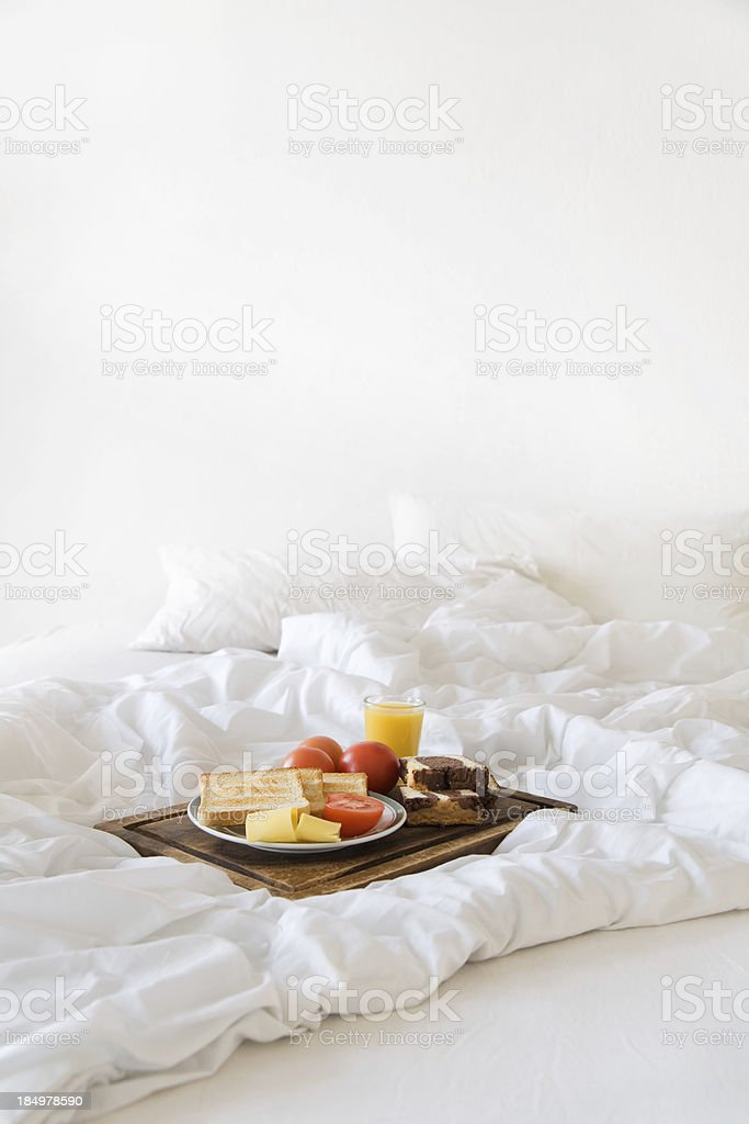 Breakfast tablett on a white messy bed. royalty-free stock photo