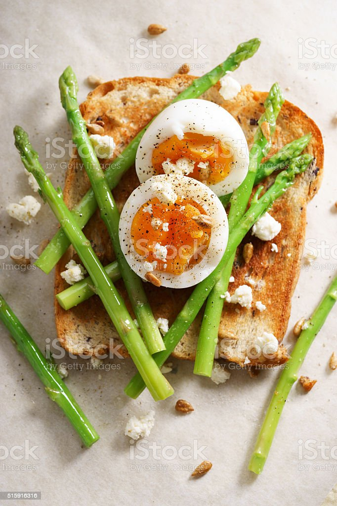 breakfast toast top with asparagus and soft boiled egg stock photo