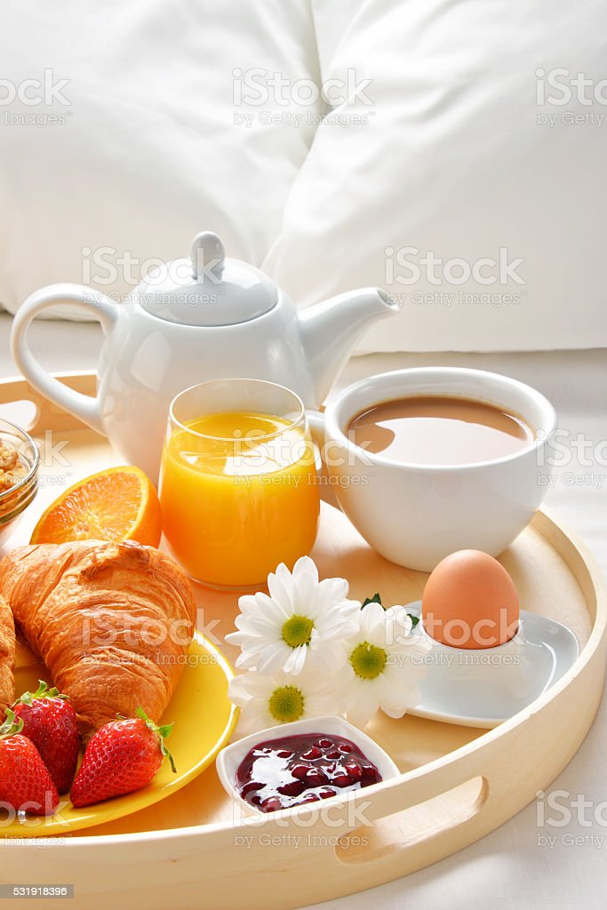 Breakfast tray in bed in hotel room stock photo