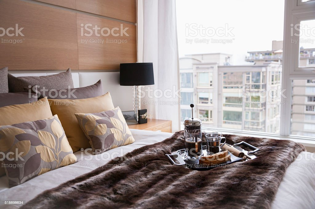 Breakfast tray on comfortable bed by large window stock photo