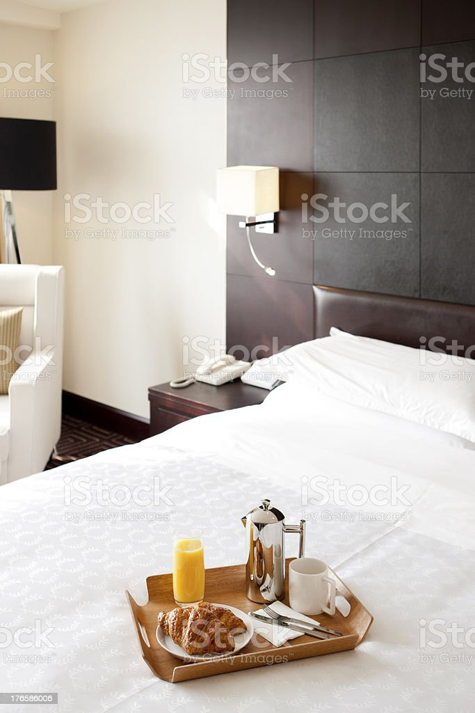Breakfast tray resting on clean white bed spread royalty-free stock photo