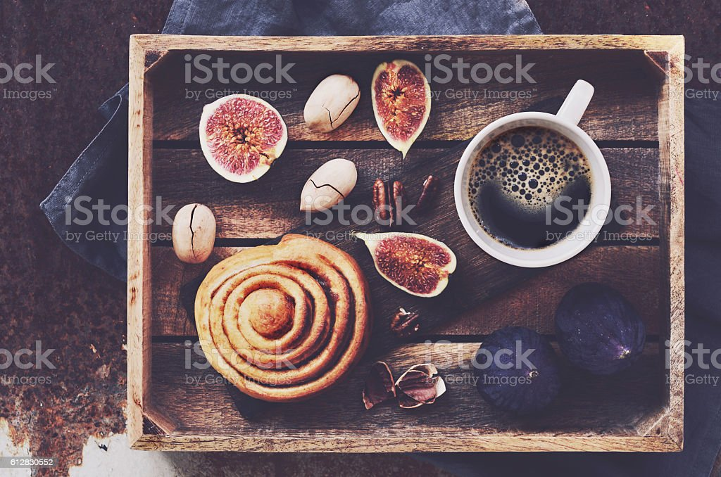 Breakfast tray with espresso, cinnamon roll, figs and pecan nuts stock photo