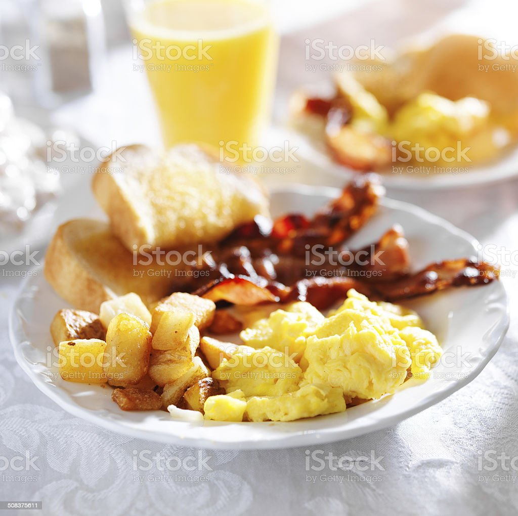 breakfast with bacon, eggs and home fries stock photo