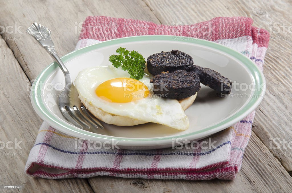 breakfast with bun, egg and black pudding stock photo