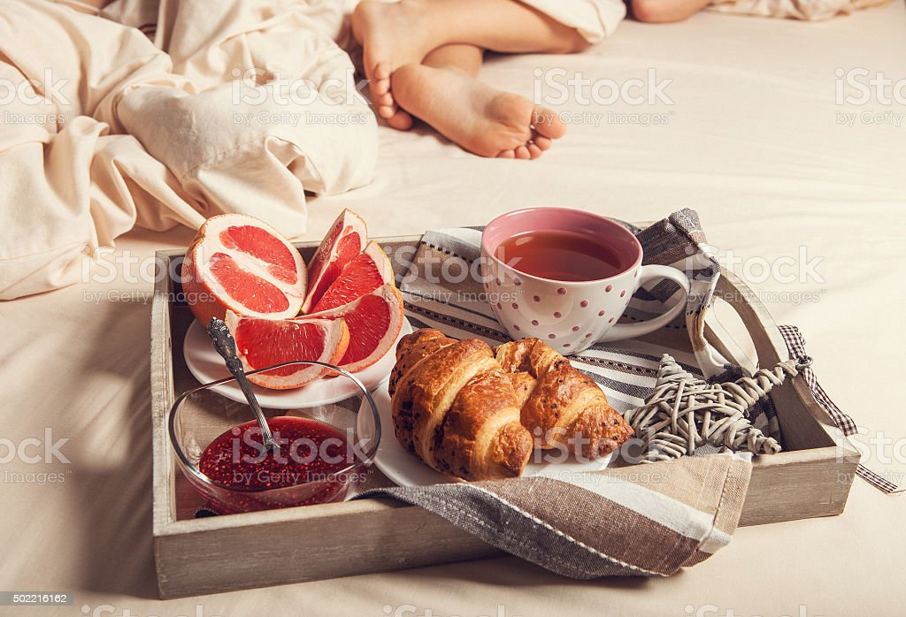 Breakfast with croissant on service tray on the bed near sleeping stock photo