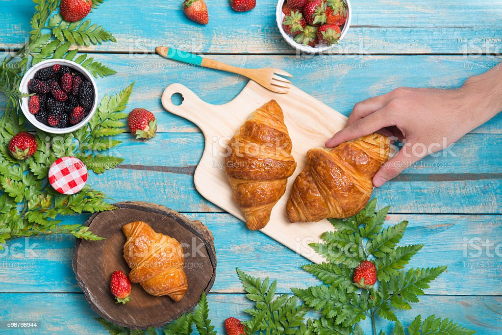 Breakfast with croissants and strawberry on blue wooden table stock photo