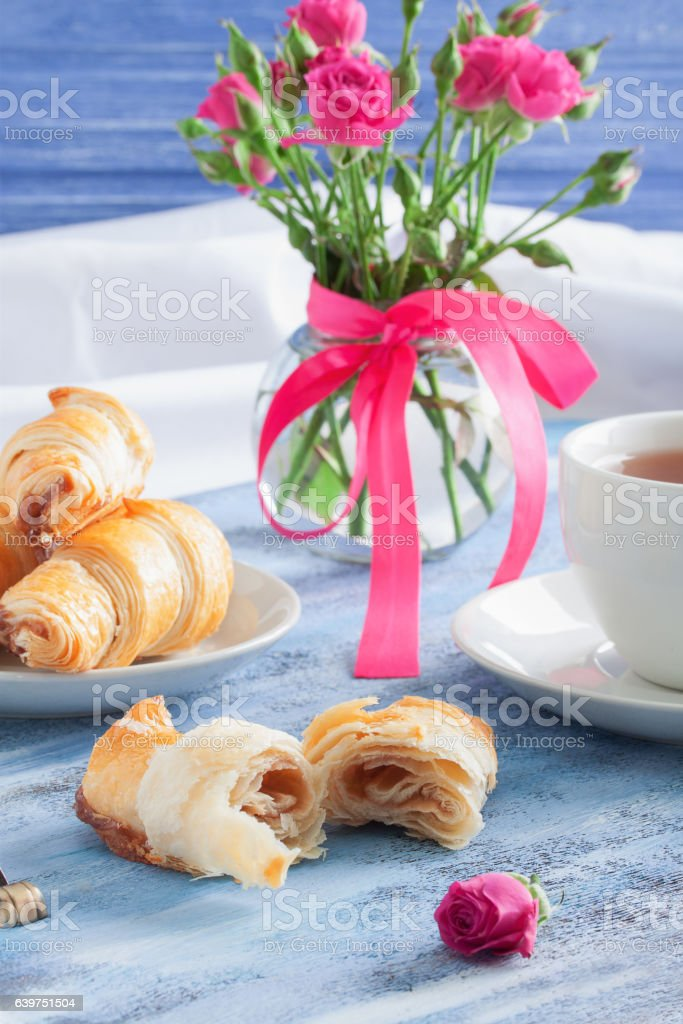 Breakfast with croissants tea and flowers on blue wooden tray. stock photo
