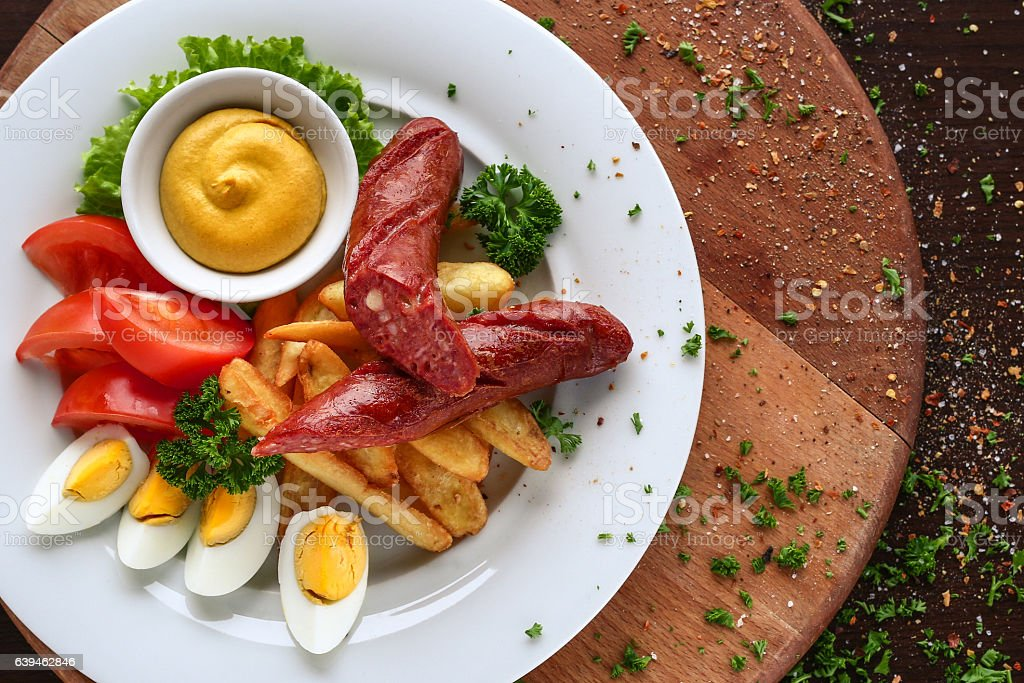 Breakfast with eggs, sausage, tomato and French fries stock photo