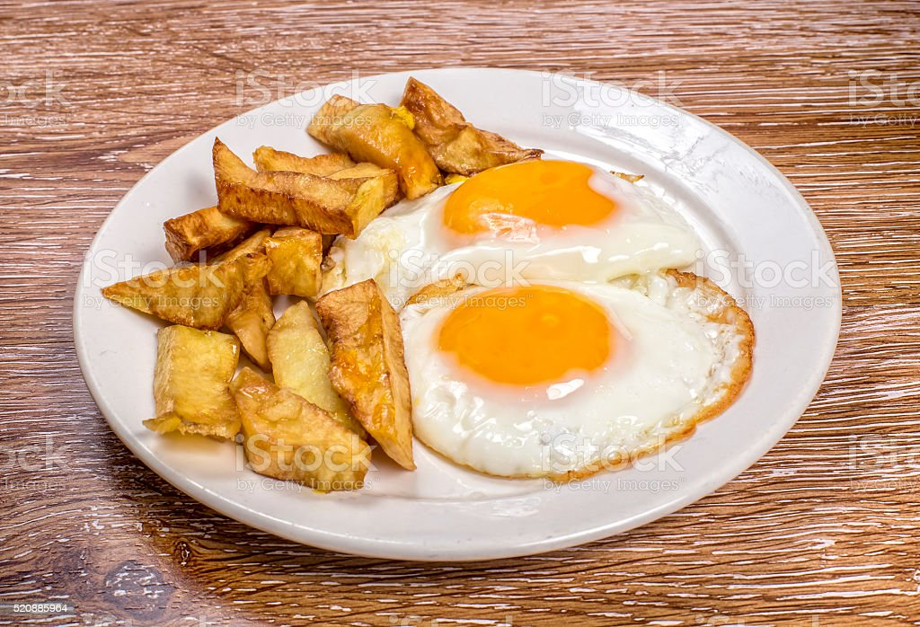 Breakfast with fried eggs and french fries on wooden background stock photo