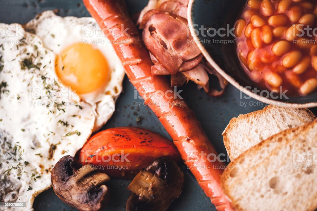 Breakfast with fried eggs, sausage, lobio, baked tomatoes and mushrooms stock photo