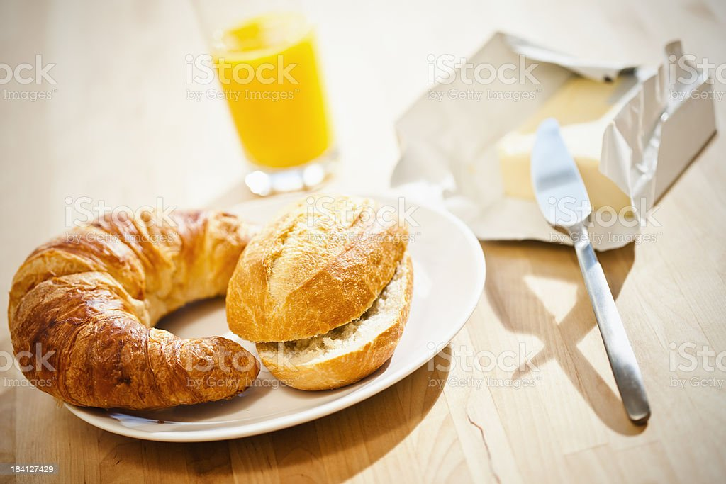 Breakfast with orange juice, croissant, butter, bun and knife on royalty-free stock photo