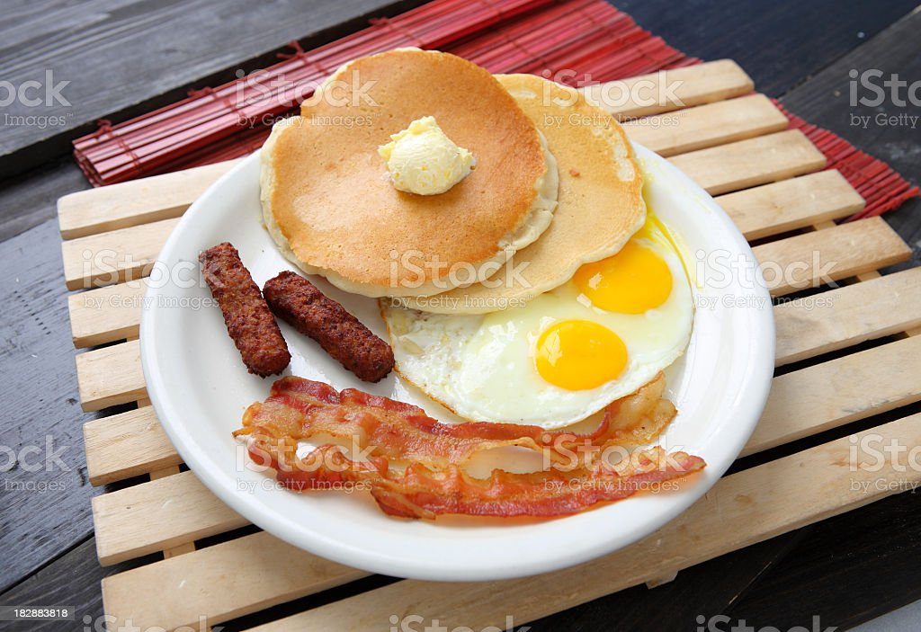 A breakfast with pancakes eggs and bacon on white plate royalty-free stock photo