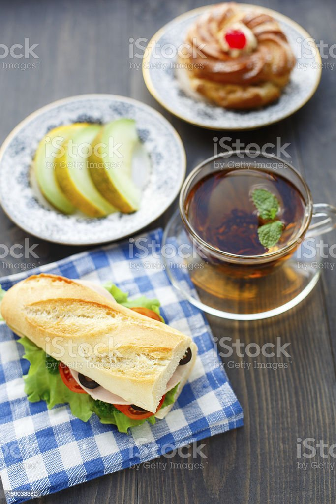 Breakfast with sandwich, tea, cake and melon royalty-free stock photo