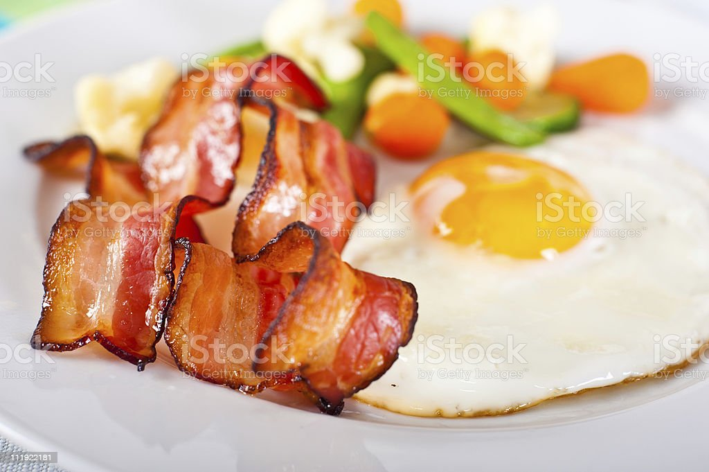 A breakfast with vegetables, bacon and sunny-side up egg stock photo
