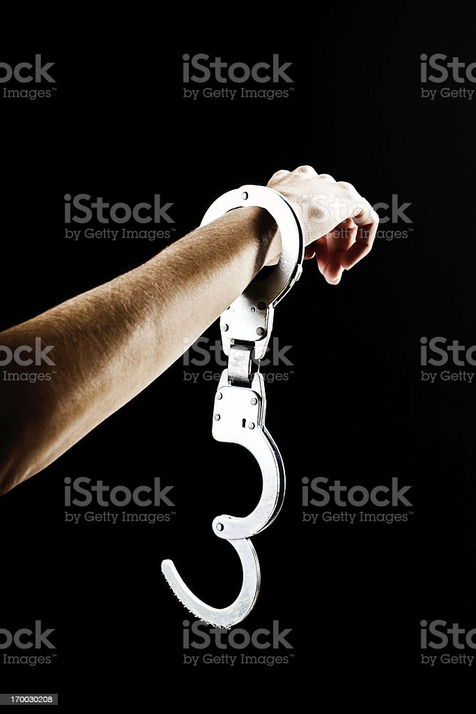 Breaking free: hand with single handcuff against black stock photo