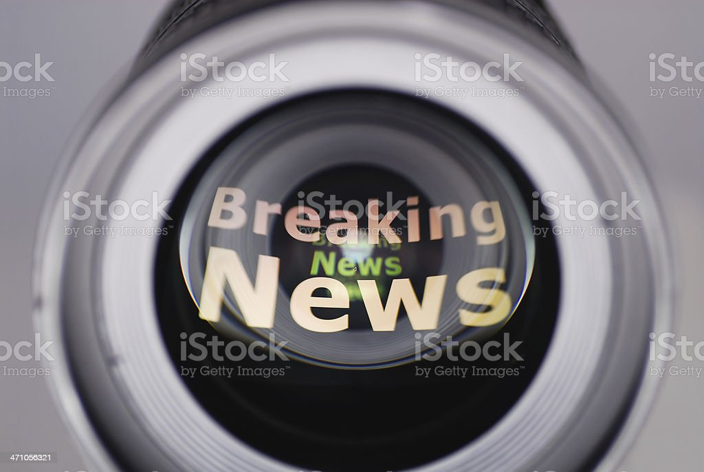 Breaking news reflected on a camera lens royalty-free stock photo
