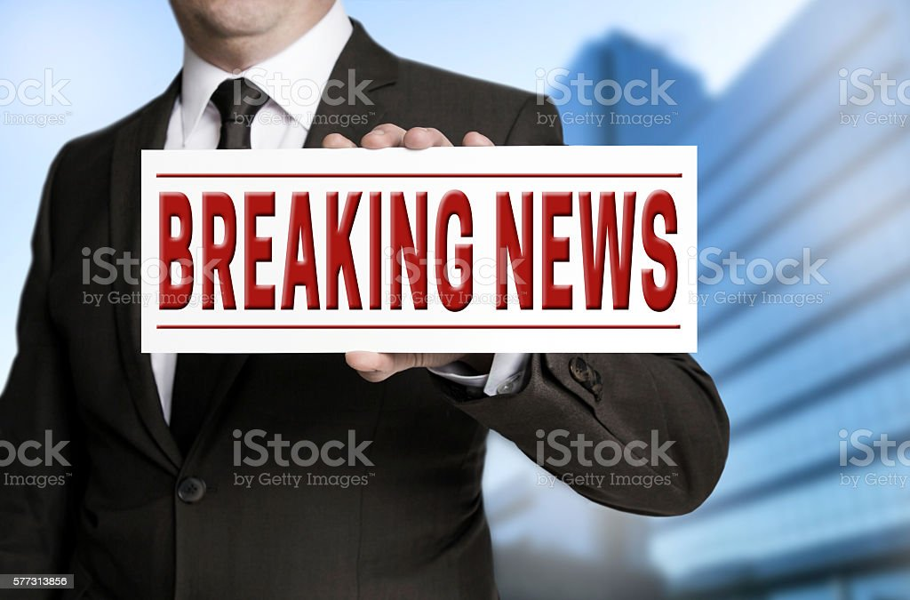 breaking news sign is held by businessman stock photo