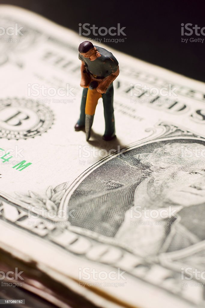 Breaking Up the Dollar - Tiny Workman royalty-free stock photo