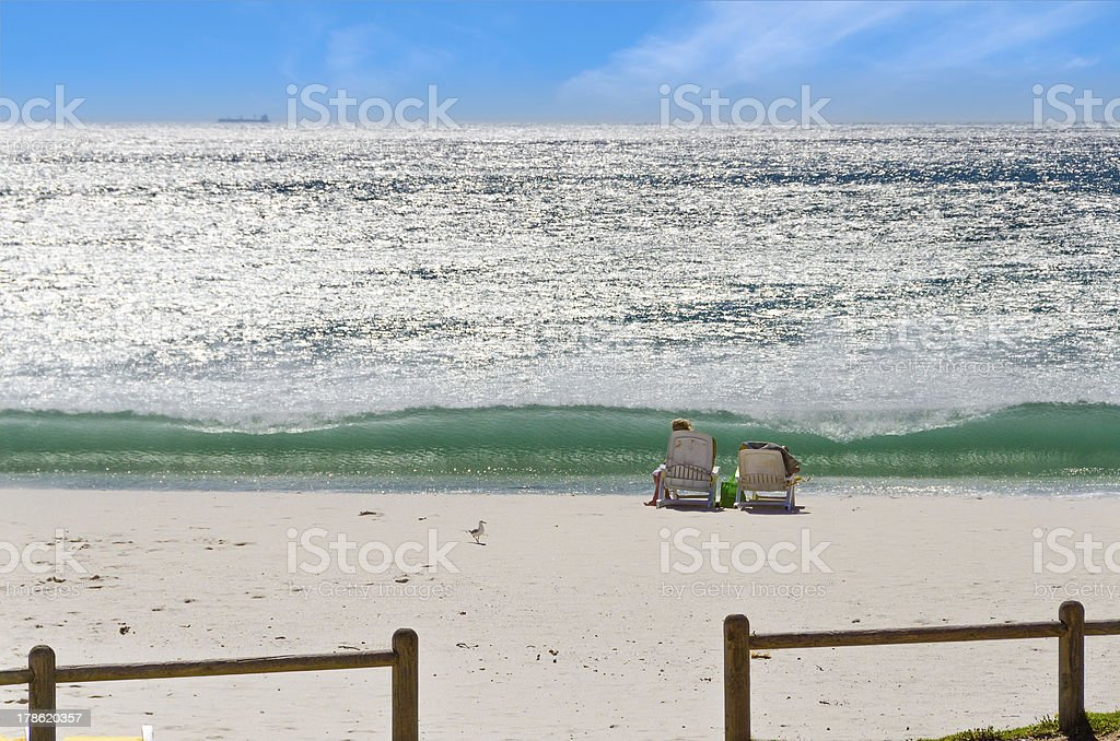 Breaking wave on beach in front of tourists stock photo