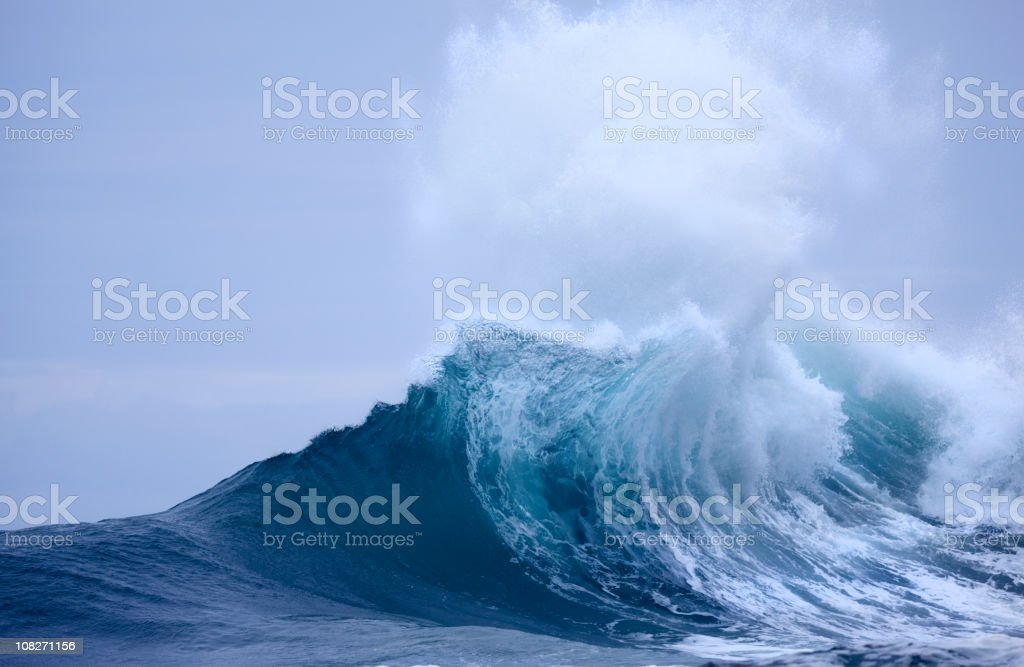 Breaking Wave with white spray and blue sky stock photo