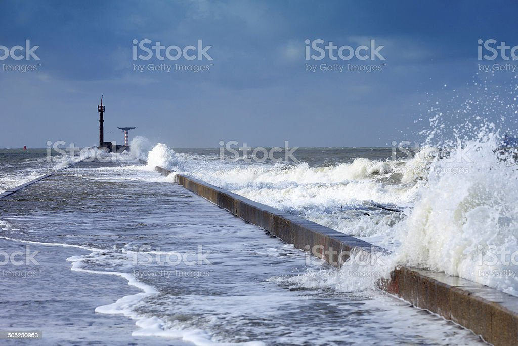 breaking waves on a jetty along the Nieuwe Waterweg river stock photo
