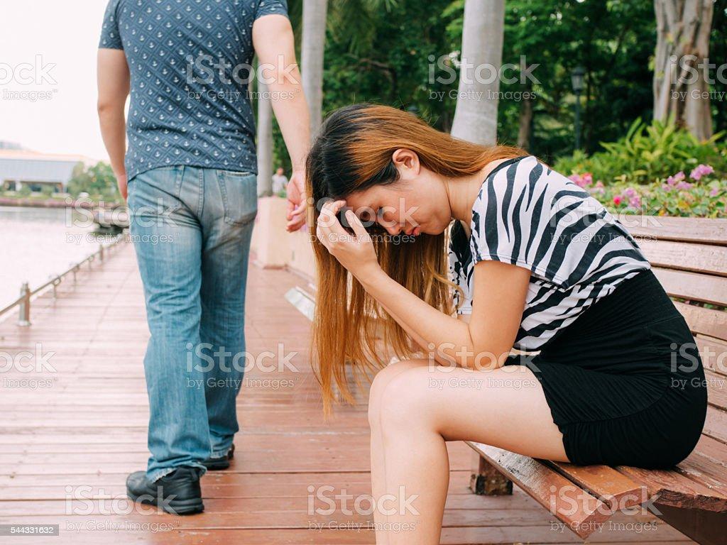 Breakup couple with sad girlfriend and boyfriend walking away stock photo