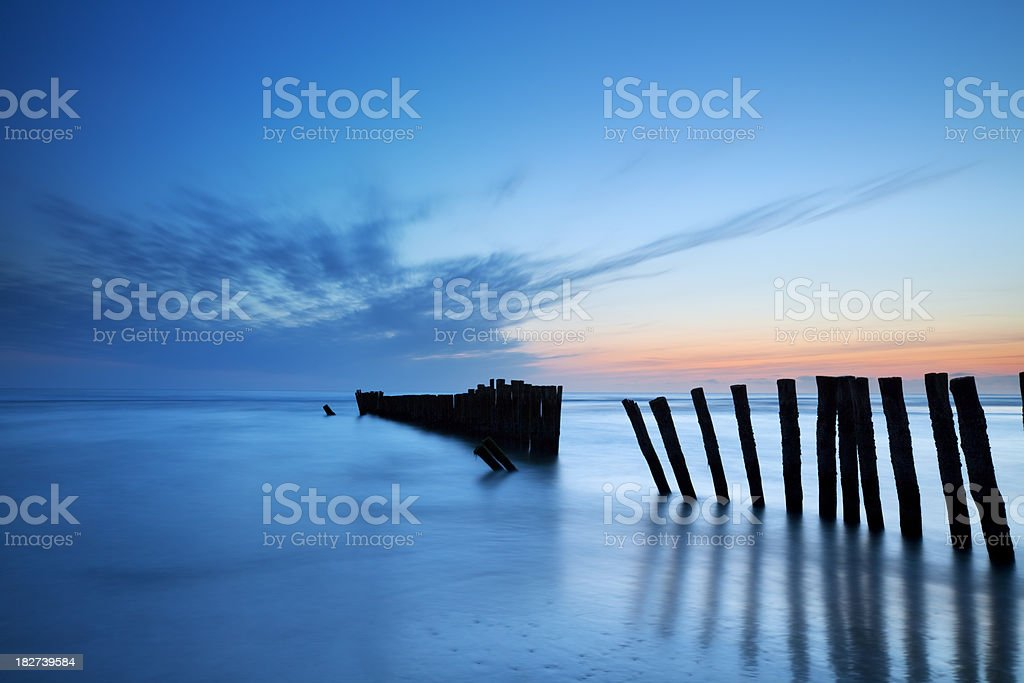 Breakwater on the beach at dusk in North-Holland, The Netherlands royalty-free stock photo