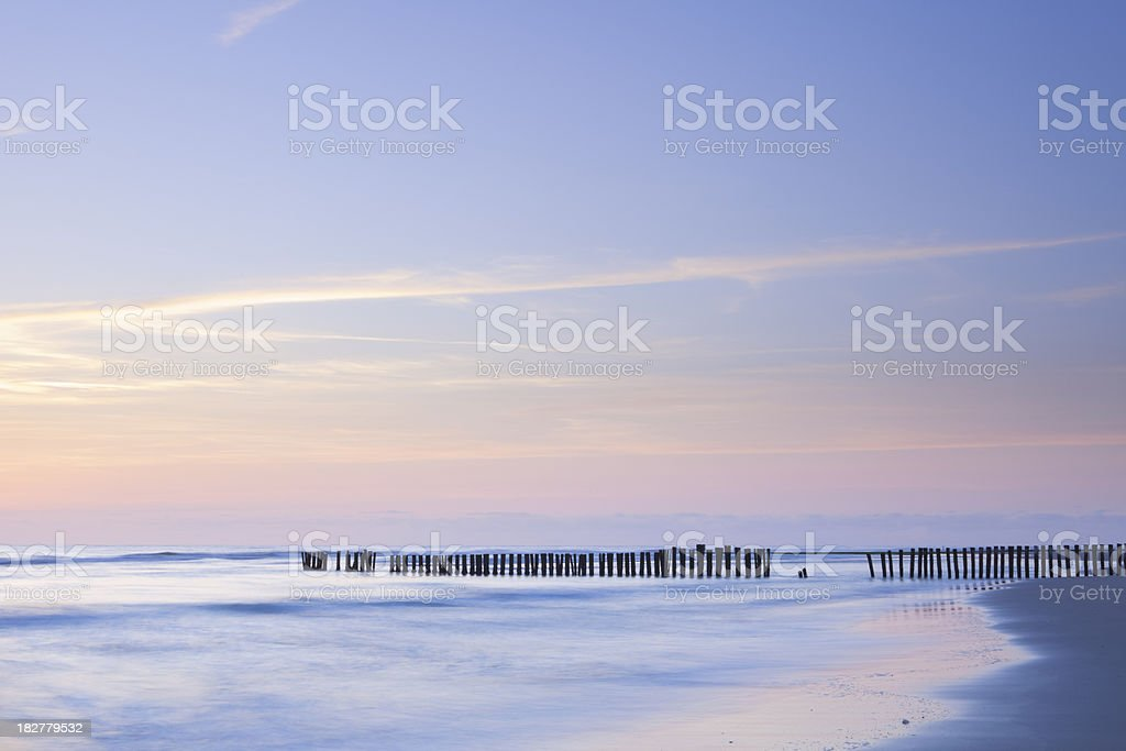 Breakwater on the beach at sunset in North-Holland, The Netherlands royalty-free stock photo