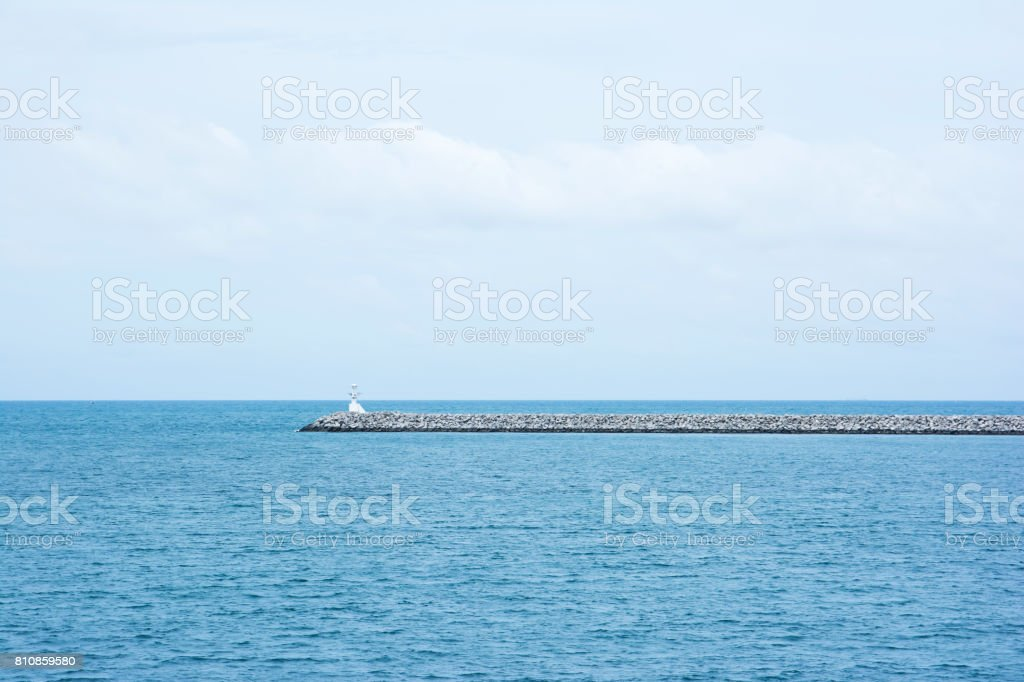Breakwater (pier) with small lighthouse. The construction wall in the port to protect the ships from sea waves. stock photo