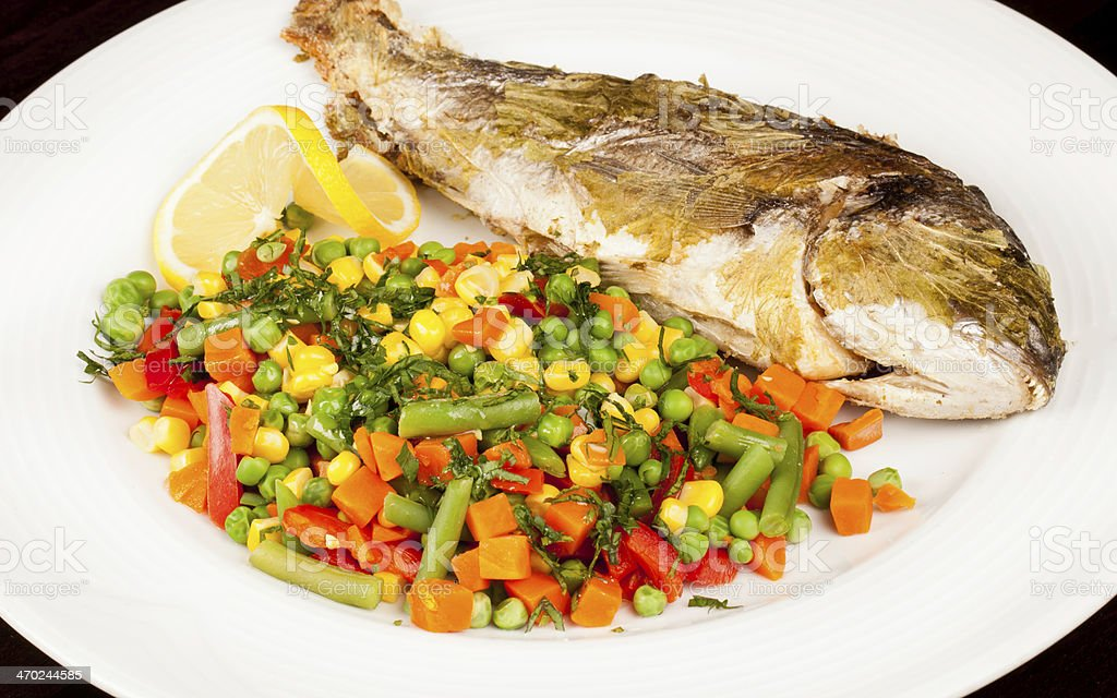Bream baked in salt jacket and mexican salad stock photo