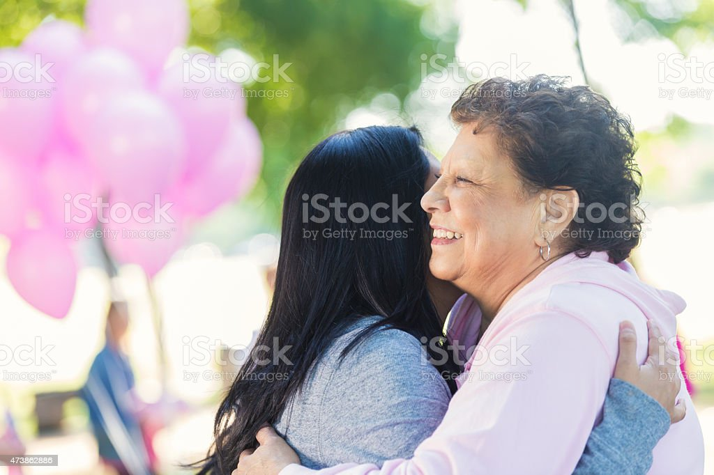 Breast cancer survivor hugging daughter after charity race stock photo