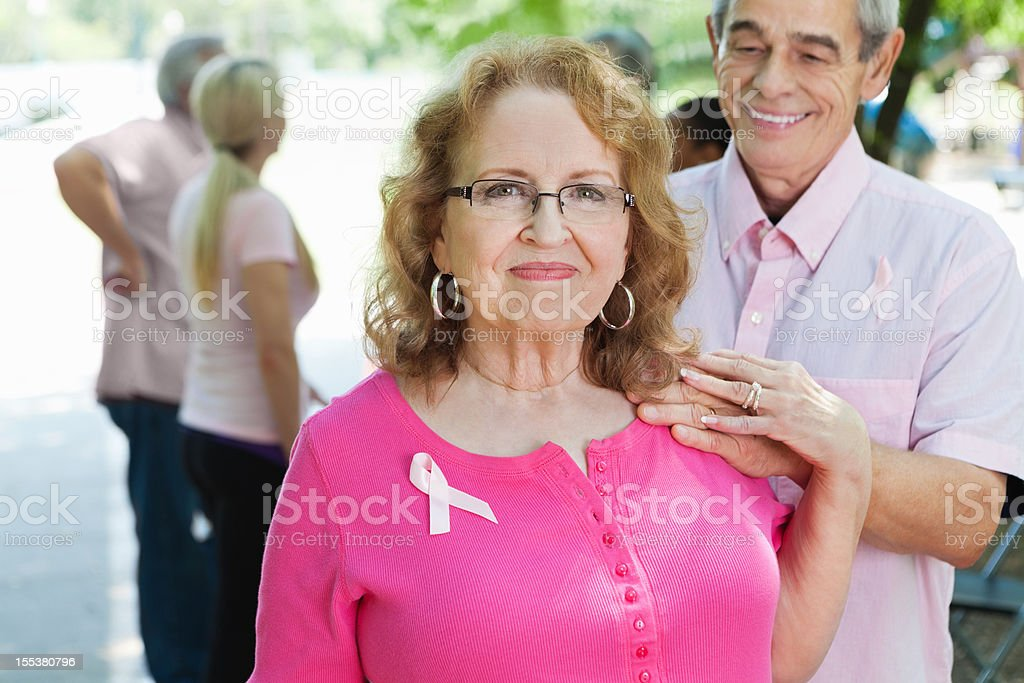 Breast cancer survivor with supportive spouse at outdoor charity race stock photo